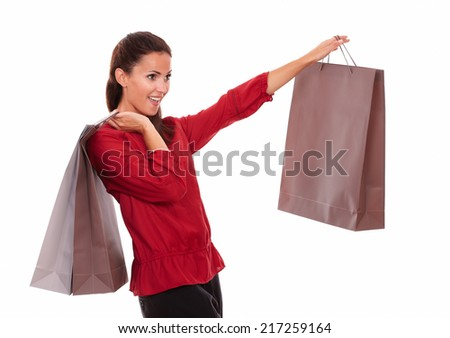 Portrait of stylish adult lady on red shirt with paper bag screaming while standing on isolated white background - copyspace - stock photo