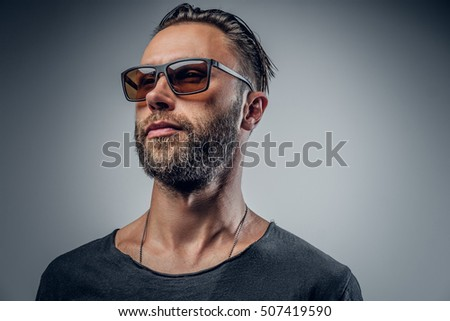 Portrait of stylish bearded male in sunglasses on grey background.