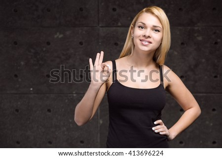 Portrait of stylish beautiful young blonde woman. Woman smiling and showing ok sign