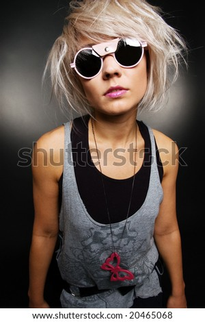 portrait of stylish casual girl in sunglasses over dark background