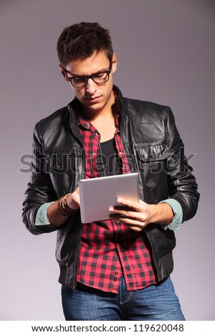 portrait of stylish casual man wearing leather jacket and glasses, working or reading on his tablet pad - stock photo