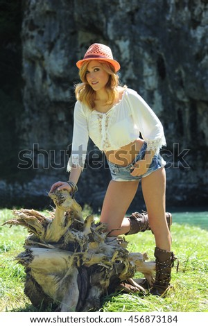 Portrait of stylish cowgirl outdoors - stock photo