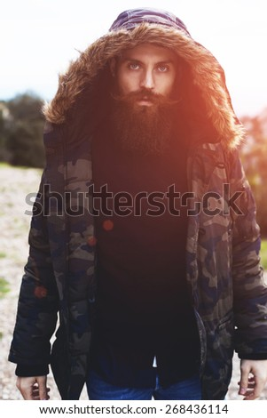 Portrait of stylish fashion handsome bearded man with beautiful blue eyes looking to the camera standing outdoors, flare sunset light - stock photo