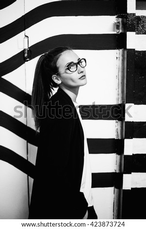 Portrait of stylish girl in black-and-white robe on a background of black-and-white wall  - stock photo