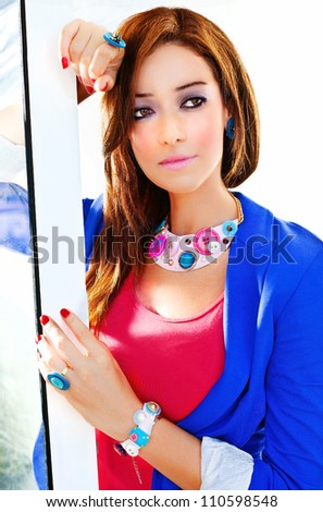 Portrait of stylish girl, young beautiful lady standing near open window, pretty woman wear pink&blue clothes and luxury colorful jewelry, fashionable glamorous makeup, attractive model posing - stock photo