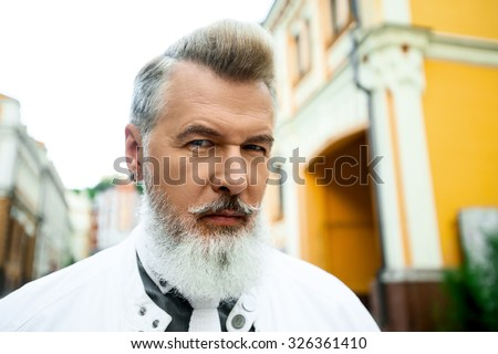 Portrait of stylish handsome adult man with beard standing outdoors. Man staring at camera - stock photo