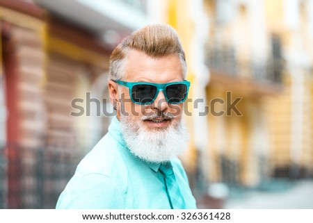 Portrait of stylish handsome adult man with beard standing outdoors. Man wearing glasses, and looking at camera - stock photo