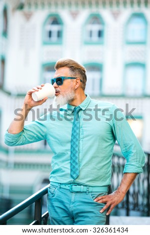 Portrait of stylish handsome adult man with beard standing outdoors. Man wearing glasses and drinking coffee - stock photo