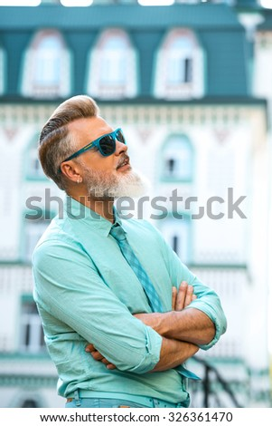 Portrait of stylish handsome adult man with beard standing outdoors. Man wearing glasses, and looking up - stock photo