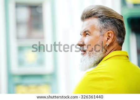 Portrait of stylish handsome adult man with beard standing outdoors. Man wearing yellow T-shirt and looking aside - stock photo