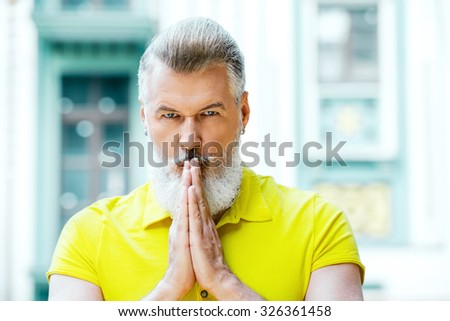 Portrait of stylish handsome adult man with beard standing outdoors. Man wearing yellow T-shirt and looking at camera while holding his hands near lips - stock photo