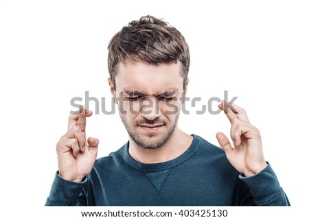 Portrait of stylish handsome young man isolated on white background. Man praying with crossed fingers