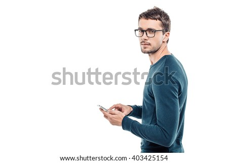 Portrait of stylish handsome young man isolated on white background. Man wearing glasses, looking at camera and using mobile phone. Back view photo - stock photo