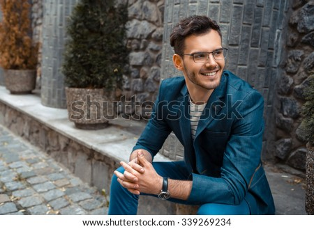 Portrait of stylish handsome young man with bristle sitting on parapet outdoors. Man wearing jacket and shirt - stock photo