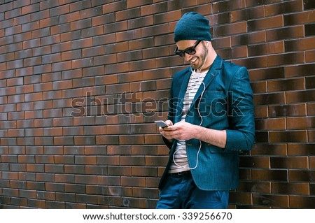Portrait of stylish handsome young man with bristle standing outdoors and leaning on brick wall. Man wearing jacket and hat. Man with sunglasses listening music on mobile phone - stock photo
