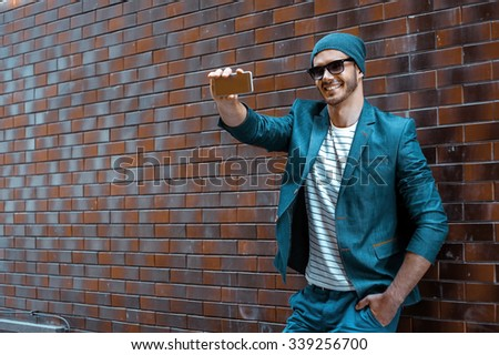 Portrait of stylish handsome young man with bristle standing outdoors and leaning on brick wall. Man wearing jacket and hat. Man making selfie with mobile phone - stock photo
