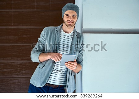Portrait of stylish handsome young man with bristle standing outdoors and leaning on wall. Young man wearing shirt and hat. Man using tablet computer and looking at camera - stock photo
