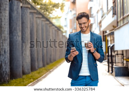 Portrait of stylish handsome young man with bristle standing outdoors. Man wearing jacket and shirt. Smiling man with glasses holding cup of coffee and using mobile phone - stock photo