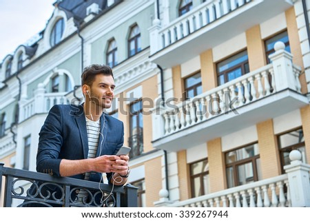 Portrait of stylish handsome young man with bristle standing outdoors. Man wearing jacket and shirt. Smiling man listening to music with mobile phone and leaning on parapet - stock photo