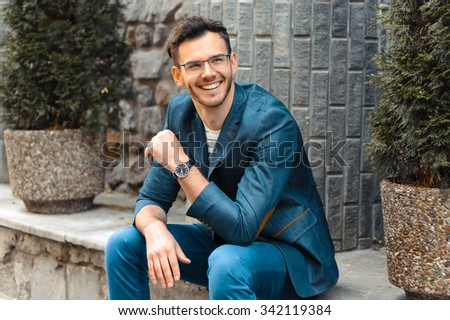 Portrait of stylish handsome young man with bristle standing outdoors. Man wearing jacket and watch. Man with glasses cheerfully smiling - stock photo
