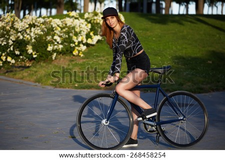 Portrait of stylish hipster girl standing with her sport fixed gear bike in the park, young  pretty woman ready to ride outside on her bicycle, promenade at sunny afternoon in summer, urban culture - stock photo