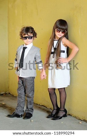 portrait of stylish little boy and girl outdoors - stock photo
