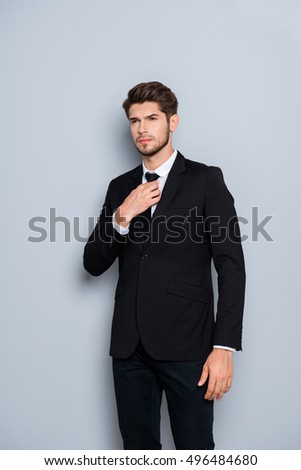 Portrait of stylish man in black suit correcting tie