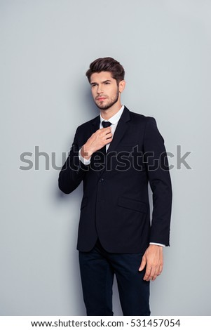 Portrait of stylish man in black suit correcting tie.