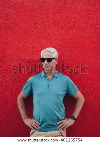 Portrait of stylish mature man standing with his hands on hips against red background. Middle aged male wearing smart watch and sunglasses posing against red wall. - stock photo
