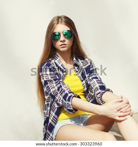 Portrait of stylish pretty young woman wearing a sunglasses and shirt outdoors - stock photo