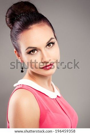 Portrait of stylish retro dressed female model with professional makeup and hairstyle. Young beautiful brunette woman wearing earrings posing in studio. - stock photo