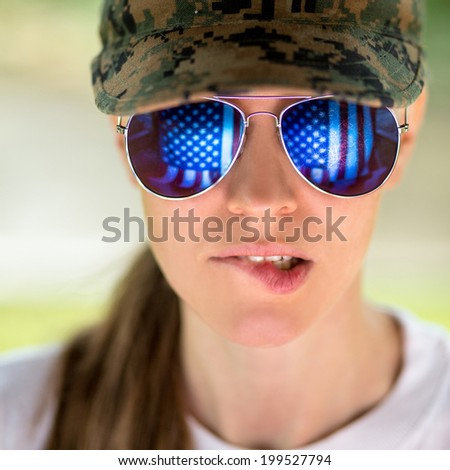 Portrait of stylish woman in military clothes wearing sunglasses with us flag in reflection - stock photo