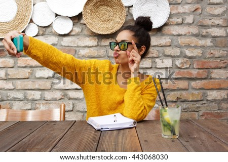 Portrait of stylish young african woman wearing sunglasses sitting at cafe and taking selfie with her smart phone - stock photo