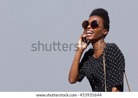 Portrait of stylish young african woman with sunglasses talking on cellphone against gray background