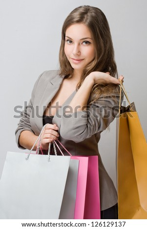 Portrait of stylish young brunette woman holding colorful shopping bags.