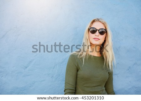Portrait of stylish young female with sunglasses standing against blue wall and looking at camera. Attractive young caucasian female model with copy space. - stock photo