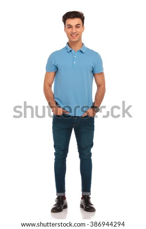 portrait of stylish young man in blue shirt posing with hands in pockets looking at the camera in isolated studio background