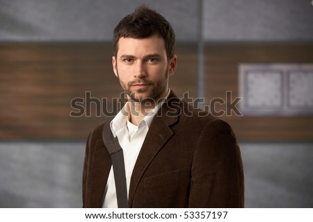 Portrait of stylish young man looking at camera in office lobby. - stock photo