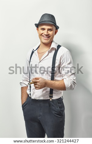 Portrait of stylish young man with cigar on white