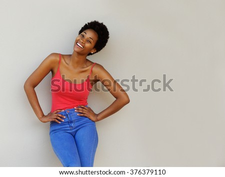 Portrait of stylish young woman standing with her hands on her hips while standing against a wall - stock photo