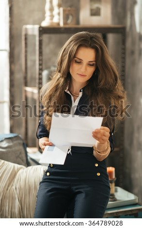 Portrait of stylish young woman with brown hairs reading letter in loft apartment - stock photo