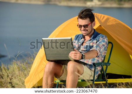 Portrait of succesful man with laptop sitting in folding chair near camp tent outdoors - stock photo