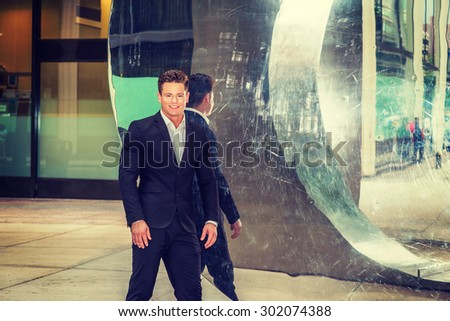 Portrait of Successful American Businessman. Dressing in black suit, a young, strong, sexy guy standing by metal mirror wall, smiling, confidently looking forward. Instagram filtered effect. - stock photo
