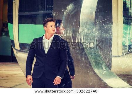 Portrait of Successful American Businessman. Dressing in black suit, a young, strong, sexy guy standing by metal mirror wall, looking away, confidently looking forward. Instagram filtered effect.  - stock photo