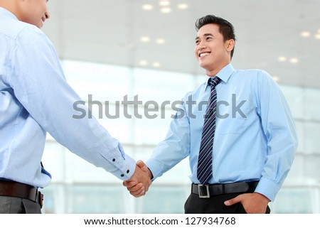 Portrait of successful business man shaking hands with eachother in the office - stock photo