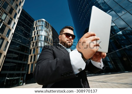 Portrait of successful business man using touch pad while standing in city financial street background, adult man in suit reads technology news on tablet pc at sunny day outdoors
