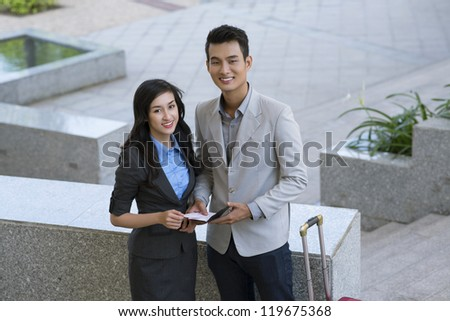 Portrait of successful business partners looking at camera outside - stock photo