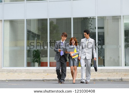Portrait of successful business partners walking in urban environment - stock photo
