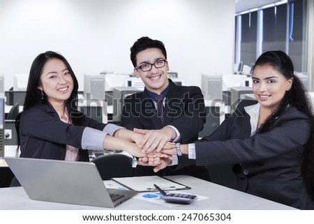 Portrait of successful business team smiling at the camera while joining their hands in the office - stock photo