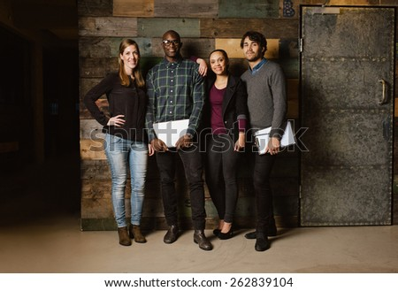 Portrait of successful business team standing together against wooden wall. Full length image of a group of diverse colleagues standing in an office - stock photo